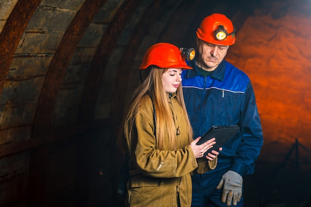 Een mooi jong meisje in een rode helm en met een elektronische tablet in haar handen
