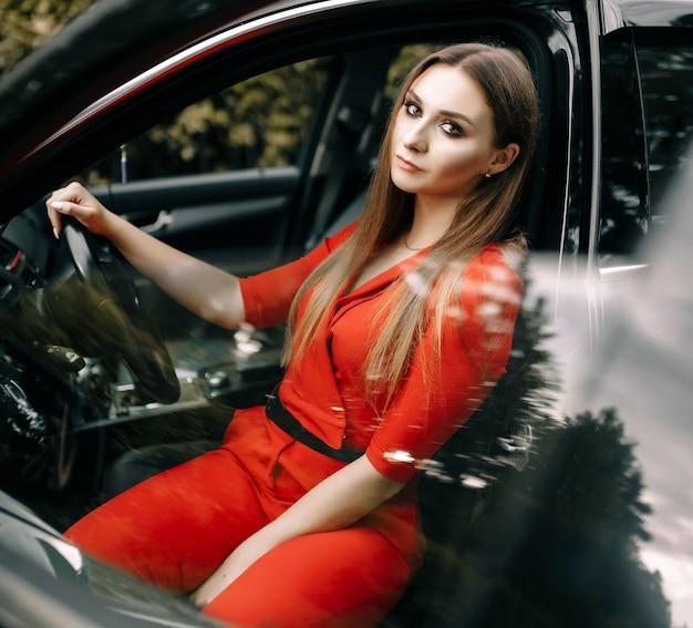 Een mooi jong meisje in een rode overall zit achter het stuur van een zwarte auto op een lege weg in het bos