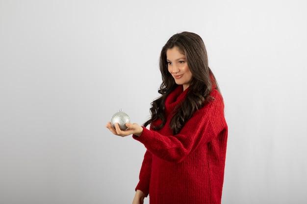 Een mooi jong meisje in een rode trui die een kerstbal geeft.