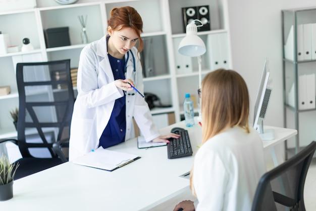 Een mooi jong meisje in een witte robe staat bij een computerbureau op kantoor en communiceert met de gesprekspartner. het meisje maakt aantekeningen in het document.