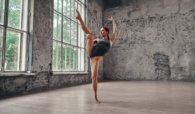 Een mooi jong meisje in een zwempak hief haar been naar het touw. yoga-concept. turnster die oefeningen doet.