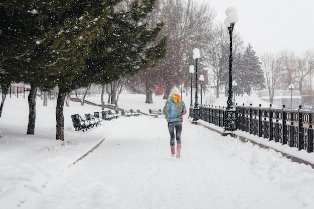 Een mooi jong meisje jogt op een ijzige en besneeuwde dag. sport, gezonde levensstijl.