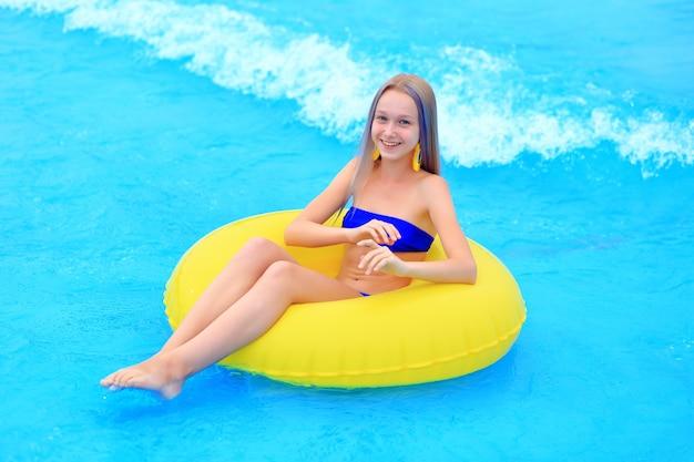 Een mooi jong meisje ligt op een opblaasbare matras in het zomer-waterpark. meisje zwemt in het zomerzwembad.
