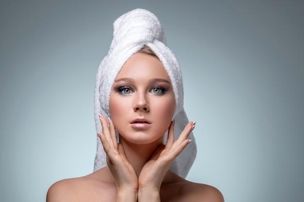 Een mooi jong meisje met een handdoek over haar hoofd na het douchen. in de studio op een grijze achtergrond.