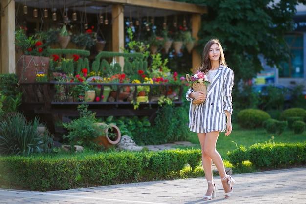 Een mooi jong meisje met lang gezond haar, in een gestreept pak, loopt over straat en heeft een rieten tas met bloemen in haar handen. het concept van levensstijl. jeugd en geluk.
