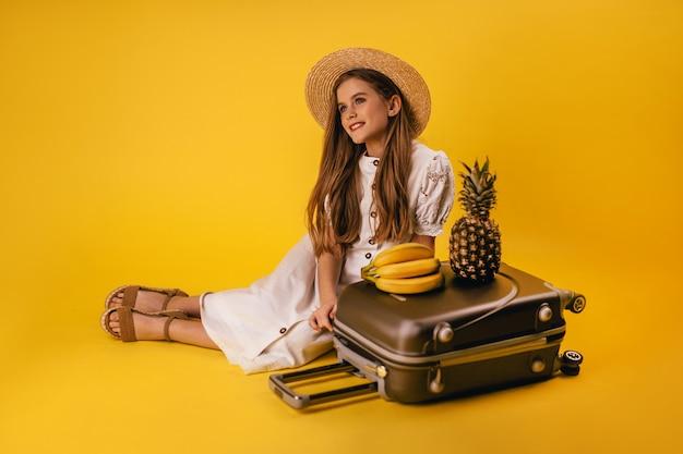 Een mooi jong meisje met lang haar heeft een reis gepland en zit in de buurt van een koffer met fruit