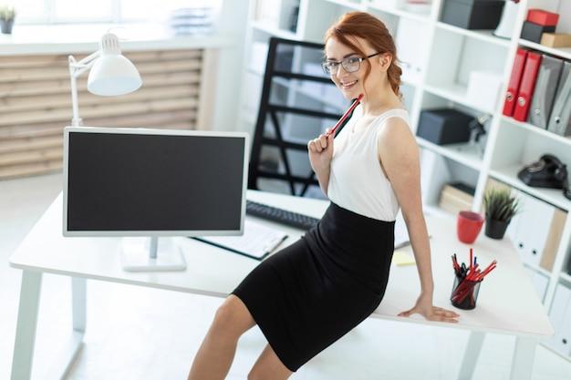 Een mooi jong meisje op kantoor ging op de tafel zitten en hield een rood potlood in haar hand.