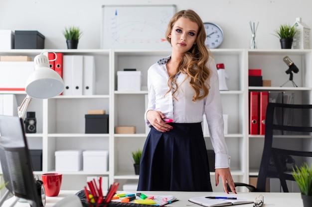 Een mooi jong meisje staat in de buurt van een tafel op kantoor en houdt een roze stift in haar hand. voor het meisje zijn er documenten.