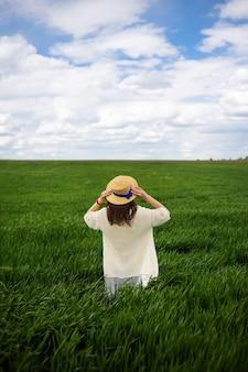 Een mooi jong meisje staat in een strohoed in een groen veld. mooie lucht.