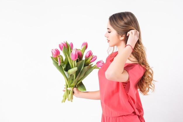 Een mooi jong meisje staat op een witte muur, draagt een roze jurk en een boeket tulpen