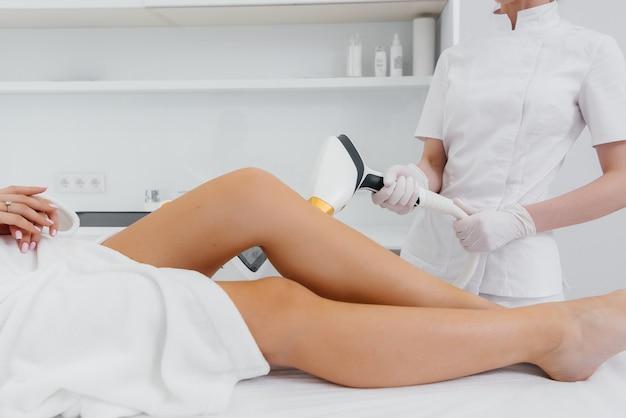 Een mooi jong meisje zal een laser ontharing procedure uitvoeren met moderne apparatuur in de spa salon close-up. schoonheidssalon. lichaamsverzorging.