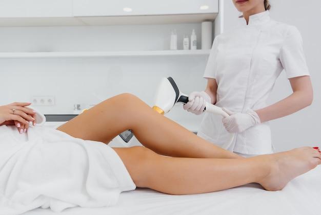 Een mooi jong meisje zal een laser ontharing procedure uitvoeren met moderne apparatuur in de spa salon. schoonheidssalon. lichaamsverzorging.