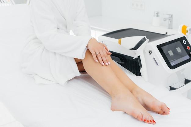 Een mooi jong meisje zal laser ontharing ondergaan met moderne apparatuur in een spa salon. schoonheidssalon. lichaamsverzorging.