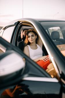Een mooi jong meisje zit 's avonds in een auto in de zonsondergang zomerzon op een lege parkeerplaats parking