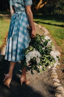 Een mooi jong model meisje in een strooien hoed vormt in een park met een boeket van witte bloeiende seringen op een zonnige lentedag Premium Foto