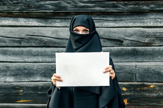 Een mooi, jong, moslimmeisje in een zwarte sluier met een gesloten gezicht tegen een grijze boom. in handsa vel papier. copyspace.