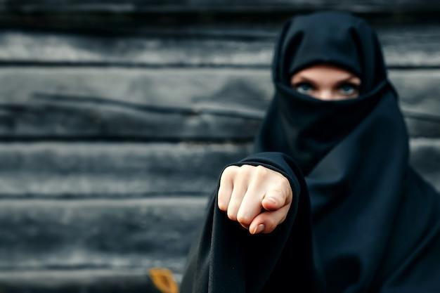 Een mooi, jong, moslimmeisje in een zwarte sluier met een gesloten gezicht tegen een grijze boom wijst haar vinger op de camera. copyspace.