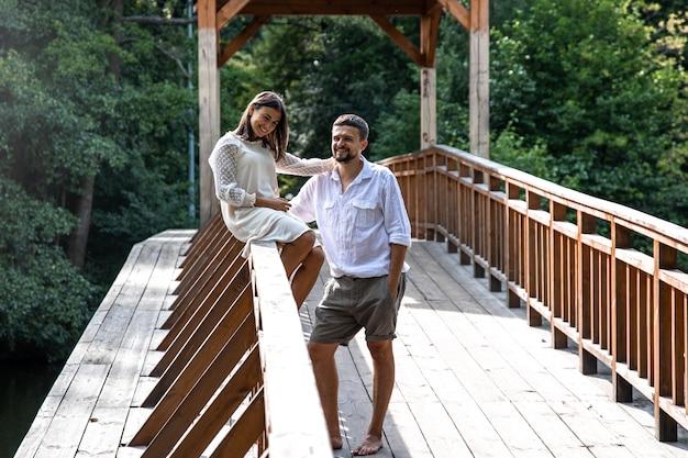Een mooi jong stel communiceert op een brug in het bos, een date in de natuur, een liefdesverhaal.