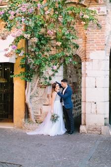 Een mooi jong stel in een bruiloft lothes vormt tegen een achtergrond van een muur van een oud huis met een bloeiende boom. sirmione, italië