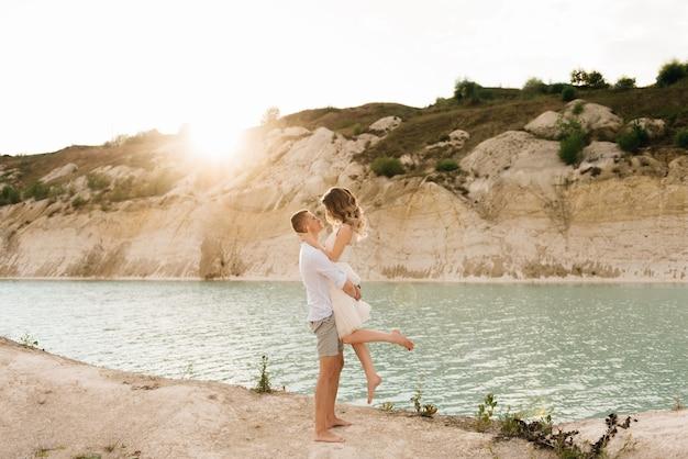 Een mooi jong verliefd stel, een man en een vrouw omhelzen elkaar, kussen bij een blauw meer en zand bij zonsondergang.
