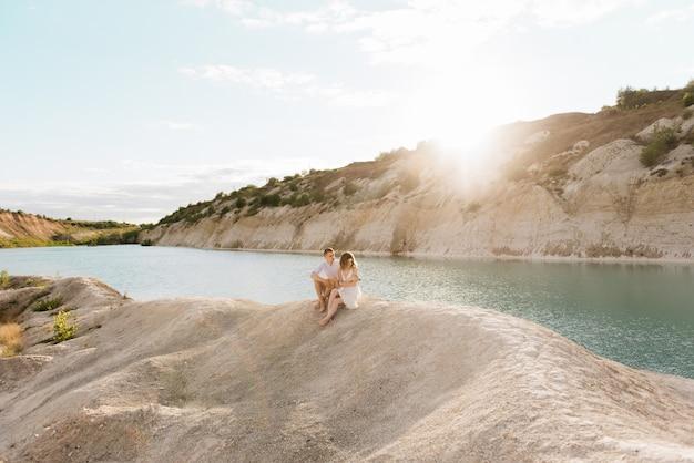 Een mooi jong verliefd stel, een man en een vrouw omhelzen, kussen in de buurt van een blauw meer en zand bij zonsondergang. vakantie aan zee op het strand