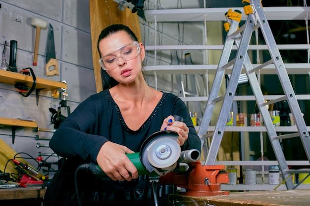 Een mooi kaukasisch meisje met haakse slijper in werkplaats met fel licht