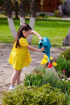 Een mooi kind geeft bloemen water uit een blauwe gieter in de tuin helpt ouders bij het verzorgen van p...