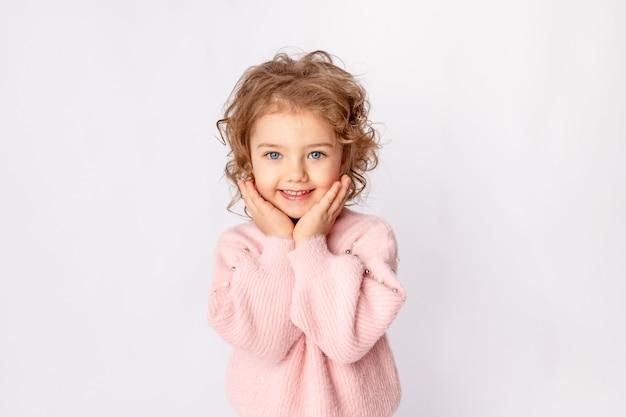 Een mooi kindmeisje op een witte geïsoleerde achtergrond in een roze trui vouwde schattige handen onder haar wangen en glimlacht, ruimte voor tekst
