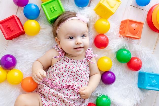 Een mooi klein babymeisje ligt in rode kleren op een witte mat onder speelgoedballen en kubussen