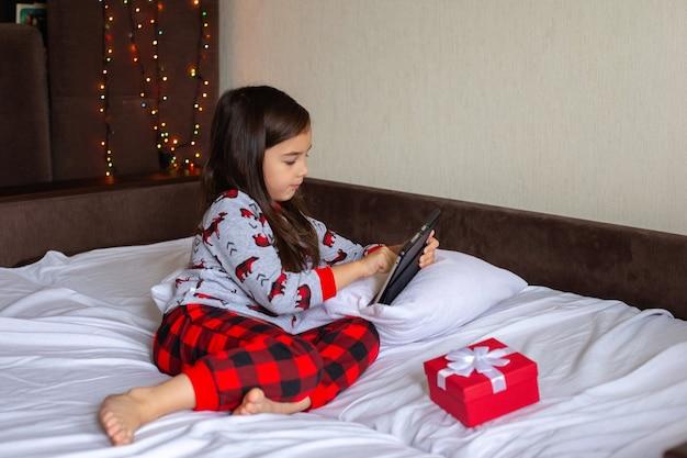 Een mooi klein brunette meisje, in een rode en grijze pyjama, ligt thuis op het bed