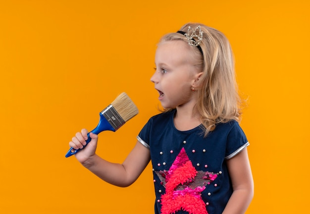 Een mooi klein meisje dat een marineblauw overhemd in een kroonhoofdband draagt, een blauwe verfborstel vasthoudt en kant op een oranje muur kijkt