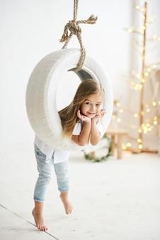 Een mooi klein meisje dat met een schommelingsboot speelt in de witte ruimte