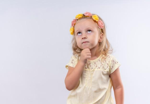 Een mooi klein meisje draagt een geel shirt in een bloemenhoofdband en denkt met de hand op de kin en kijkt omhoog op een witte muur