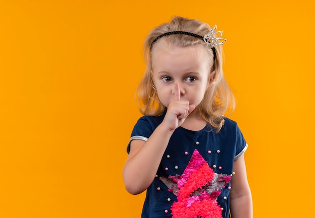 Een mooi klein meisje draagt een marineblauw shirt in kroonhoofdband met shh-gebaar met wijsvinger op de mond en kant op zoek naar een oranje muur