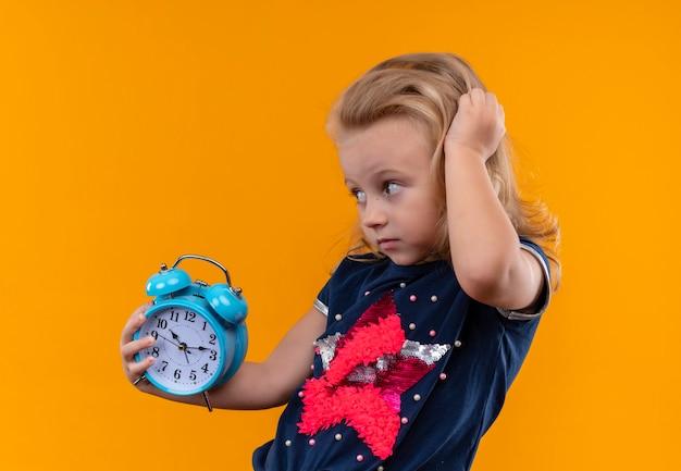 Een mooi klein meisje draagt een marineblauw shirt met een blauwe wekker terwijl ze haar hoofd op een oranje muur aanraakt