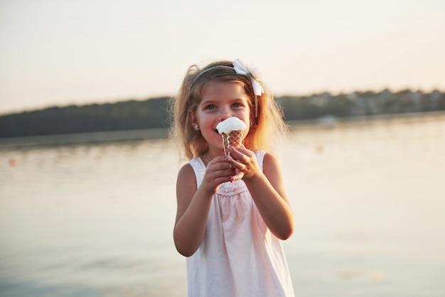 Een mooi klein meisje eet een ijsje in de buurt van het water