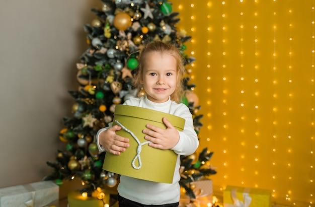 Een mooi klein meisje in een witte trui staat met een groen cadeau in de buurt van de kerstboom