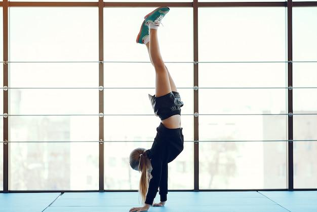 Een mooi klein meisje is bezig met een sportschool