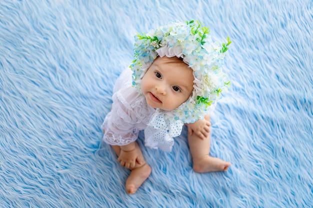 Een mooi klein meisje ligt op een blauw pluizig kleed in een hoed gemaakt van bloemen en kijkt naar de camera