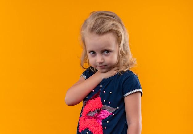 Een mooi klein meisje met blond haar dat een marineblauw overhemd draagt dat haar keel op een oranje muur houdt