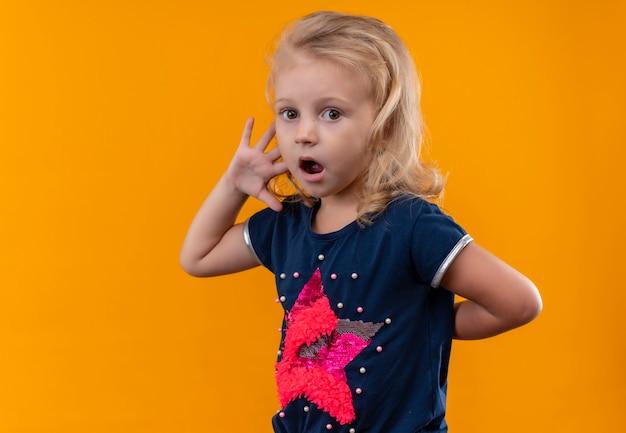 Een mooi klein meisje met blond haar dat een marineblauw overhemd draagt dat verbaasde uitdrukking toont terwijl ze op een oranje muur kijkt