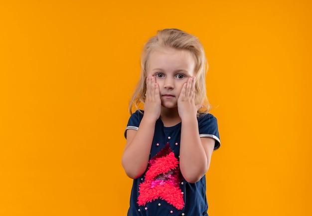 Een mooi klein meisje met blond haar dat een marineblauw overhemd draagt, hand in hand op haar gezicht op een oranje muur