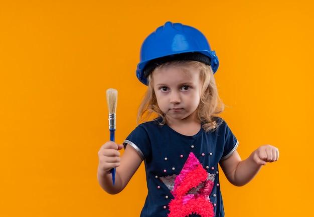 Een mooi klein meisje met blond haar dat marineblauw overhemd en blauwe helm draagt die blauwe verfborstel op een oranje muur houdt