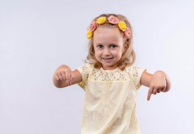 Een mooi klein meisje met een geel shirt in een bloemenhoofdband die met wijsvingers naar beneden wijst op een witte muur