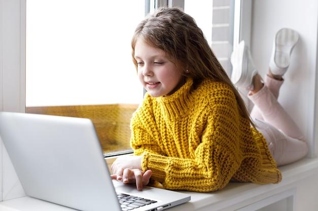 Een mooi klein meisje met een laptop thuis bij het raam kijkt naar het scherm en glimlacht