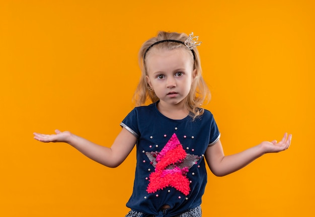 Een mooi klein meisje met een marineblauw overhemd in een hoofdband met een kroon dat verrassend met open armen op een oranje muur kijkt