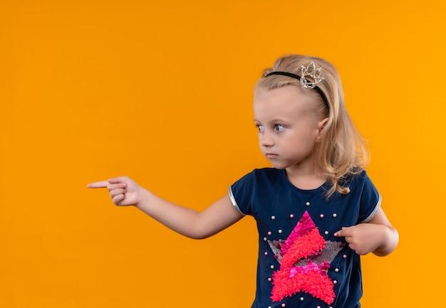 Een mooi klein meisje met een marineblauw shirt in een kroonhoofdband die met wijsvinger wijst terwijl ze op een oranje muur kijkt