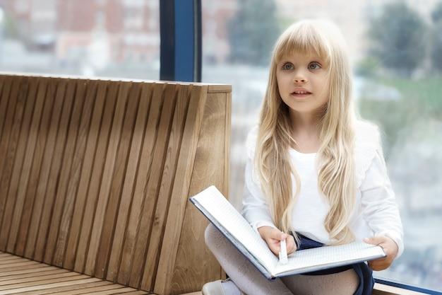 Een mooi klein meisje met grote ogen en wit haar tekent dromerig in een album bij een raam