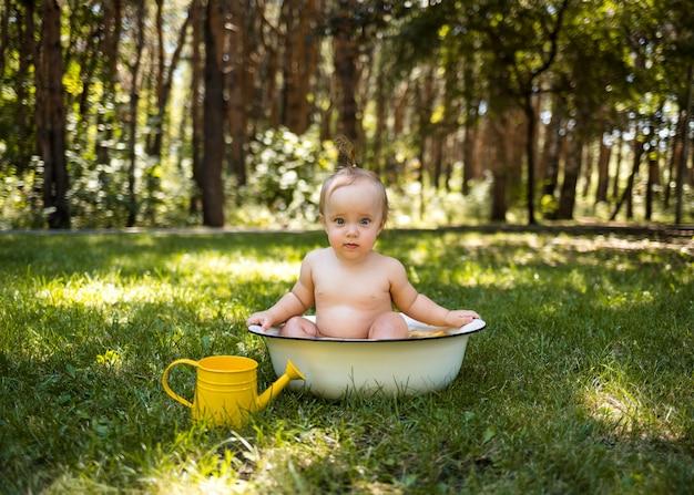 Een mooi klein meisje zit in een bad met water en een gieter en kijkt naar de camera op het groene gras