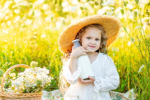 Een mooi klein meisje zit in een hoed in een geel veld met wilde bloemen en houdt een fles melk vast